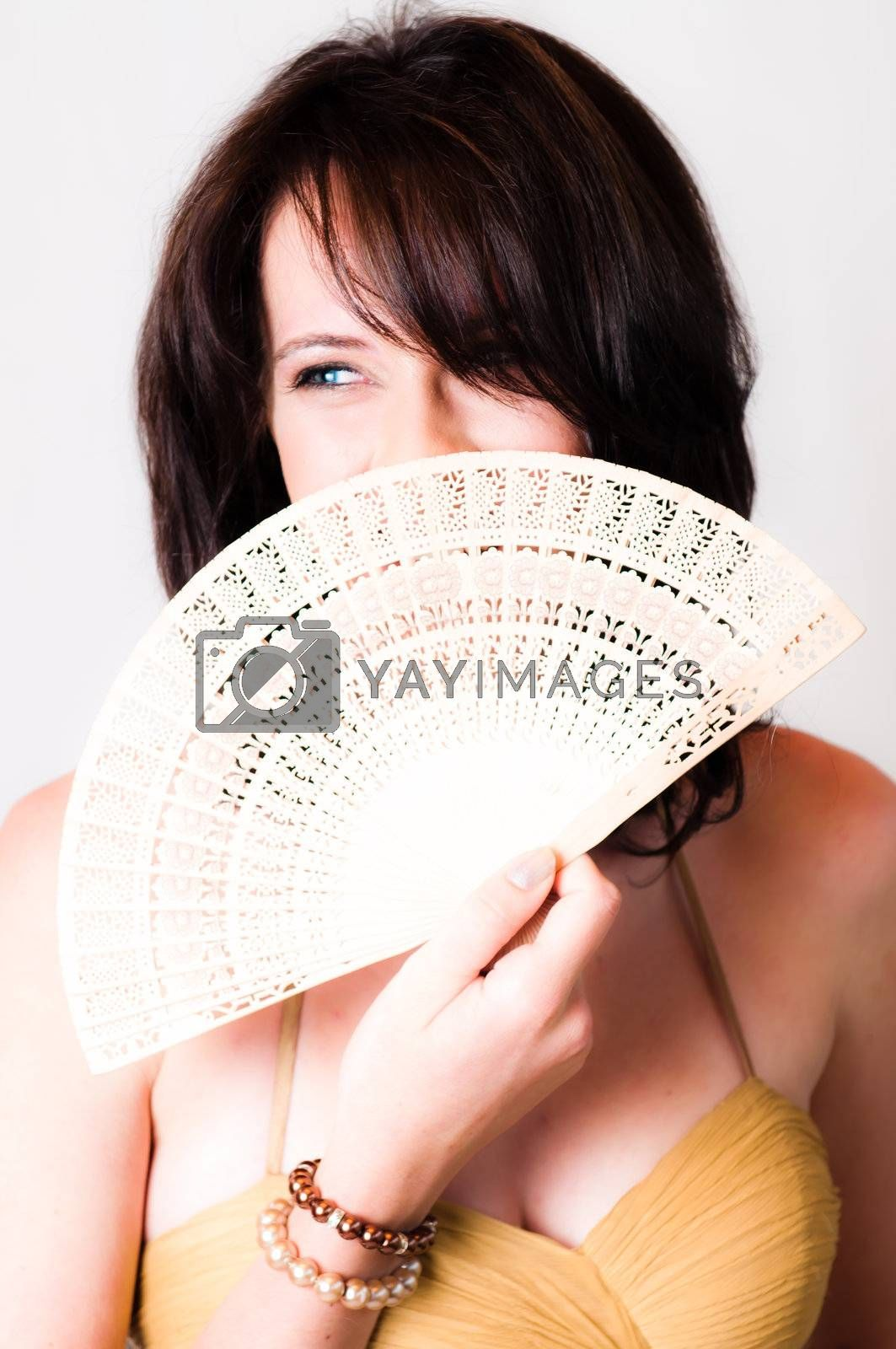 sexy image of beautiful young brunette model holding a white with Chinese hand fan in front of her face