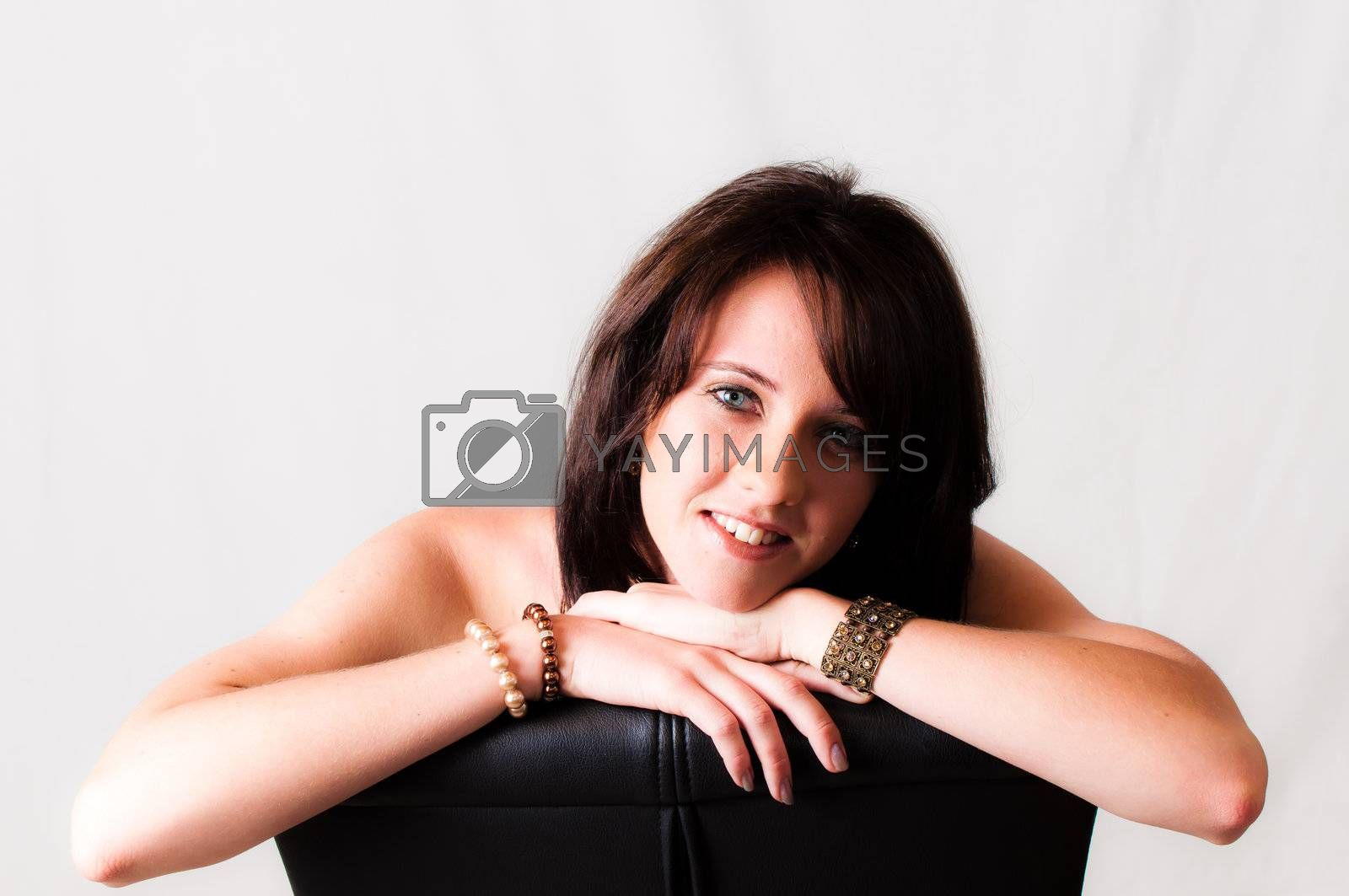 sexy image of beautiful young brunette blue eyed model sitting on a black chair with head on her hands