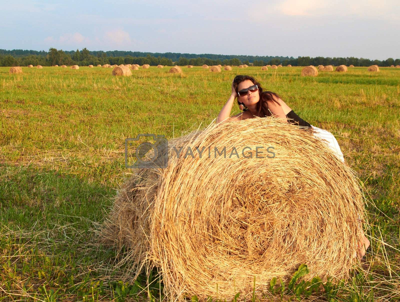 Young woman in a field lean on roll of golden hay.