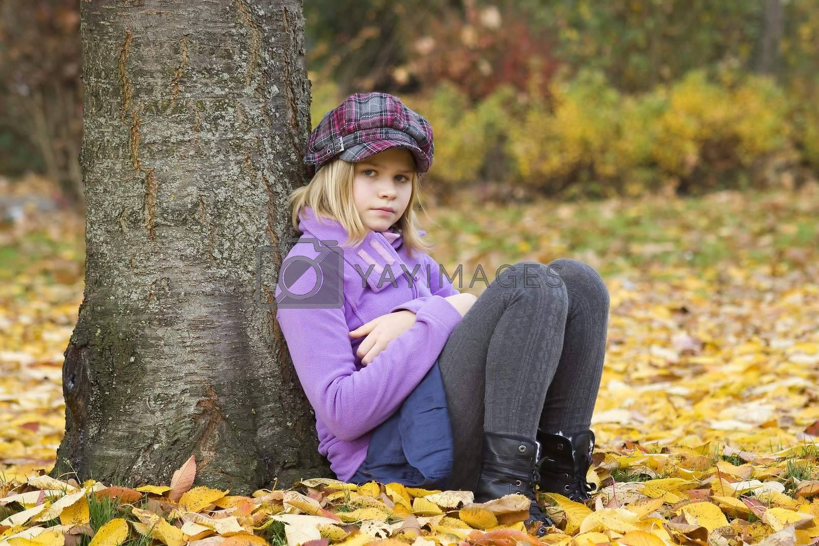 Full length portrait of a little girl sitting under tree in autumn park