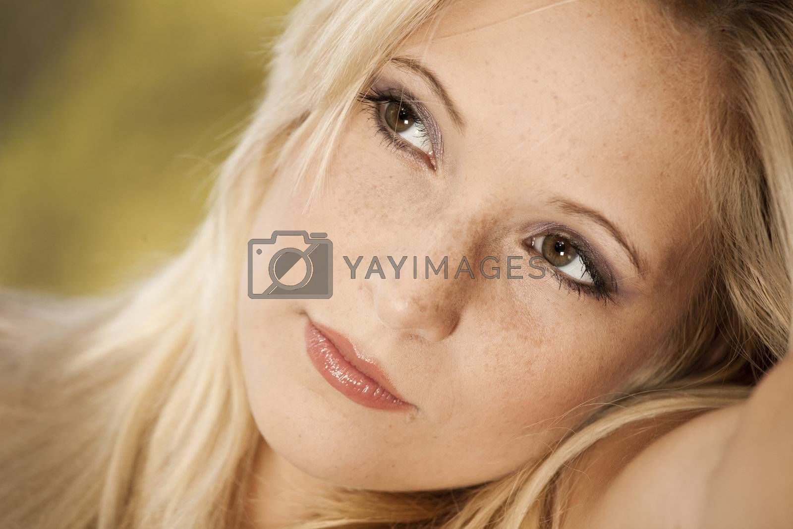 Outdoor portrait of a beautiful young woman thinking on something