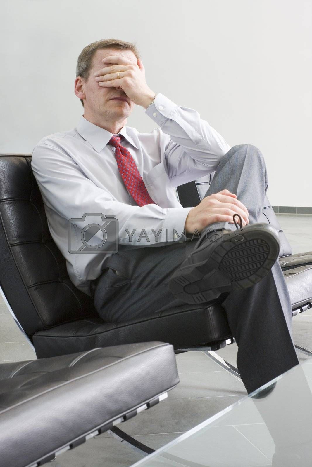 Stressed businessman sitting in a lounge