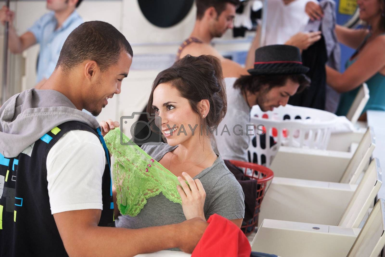 Young lady holding underwear in front of man in laundromat