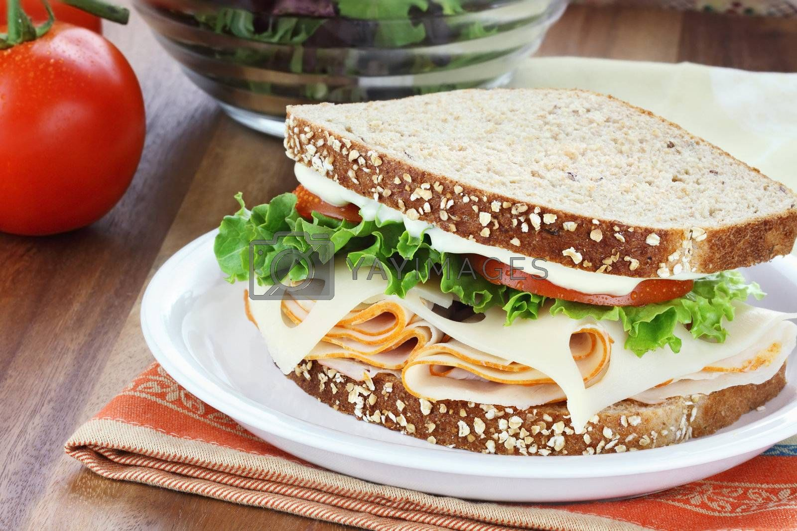 Smoked chicken sandwich with lettuce, tomato and swiss cheese and whole grain bread.