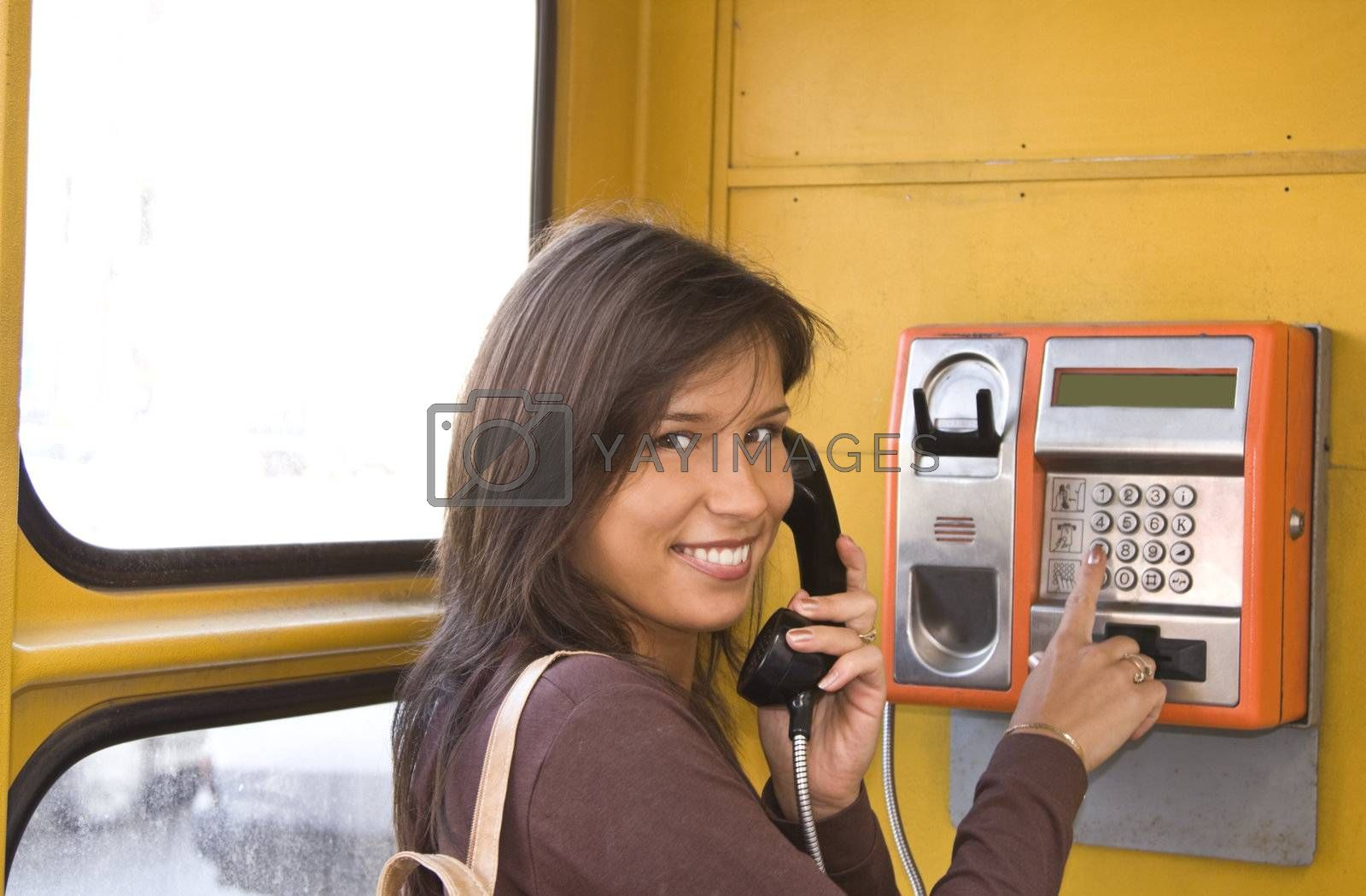 Image of a beautiful young smiling woman in a public phone cabin.