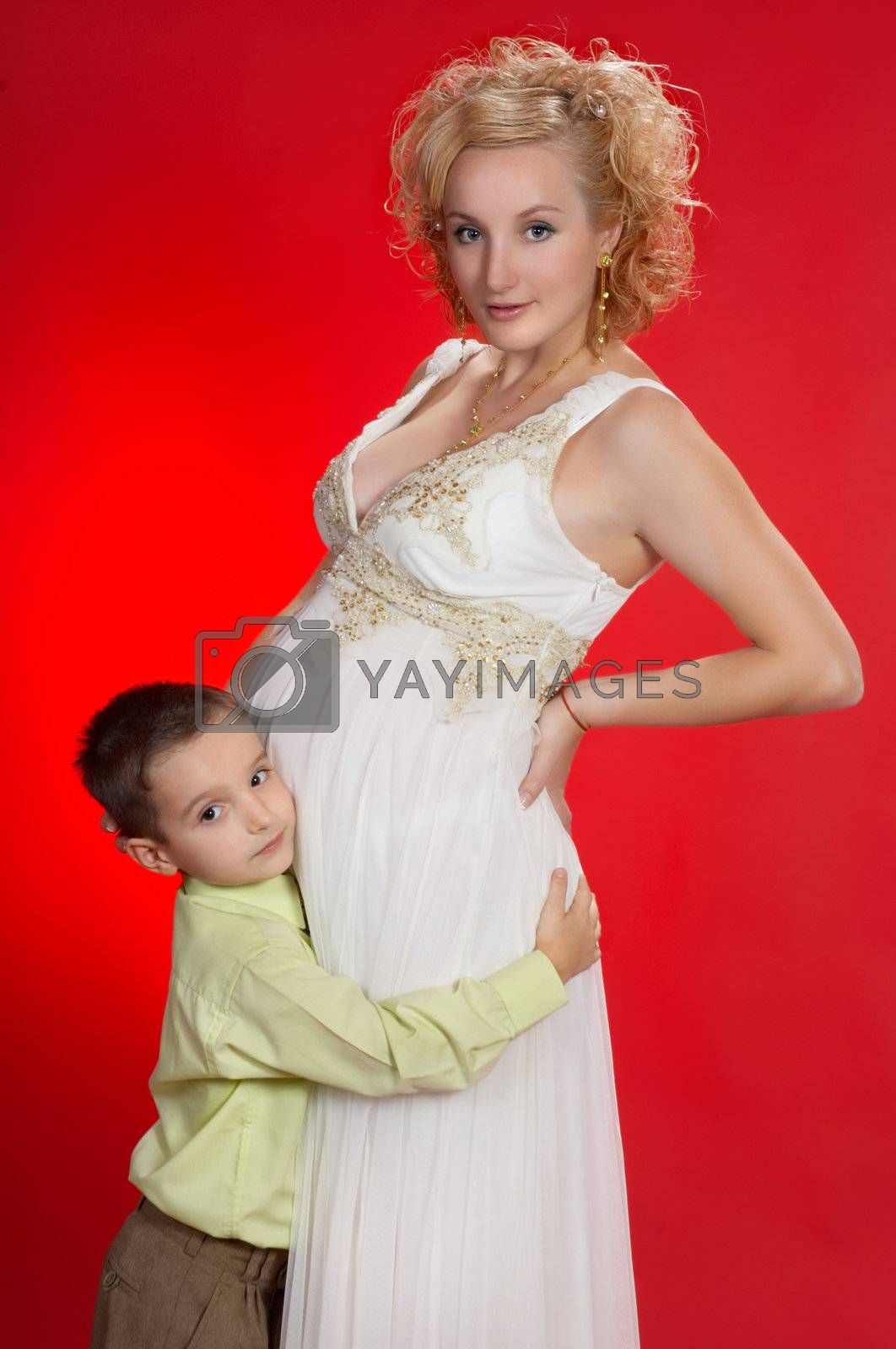 gorgeous pregnant blond woman with her first child together. on red background.