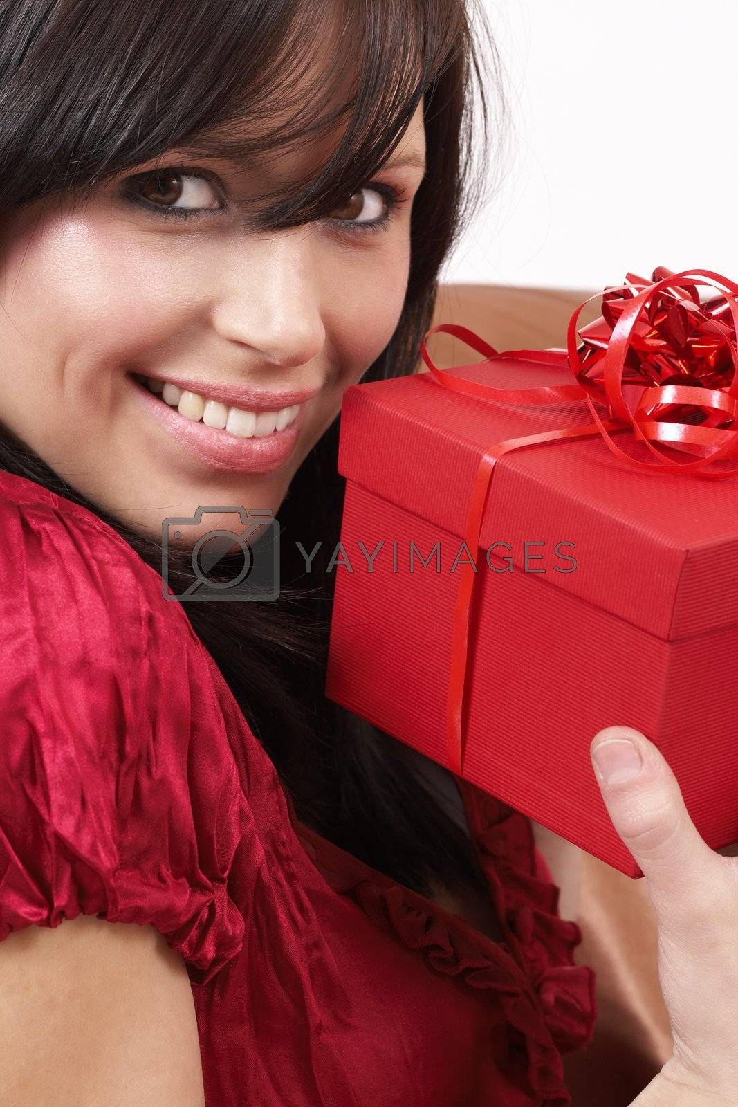 Portrait of a beautiful young brunette woman holding gift box at a celebration