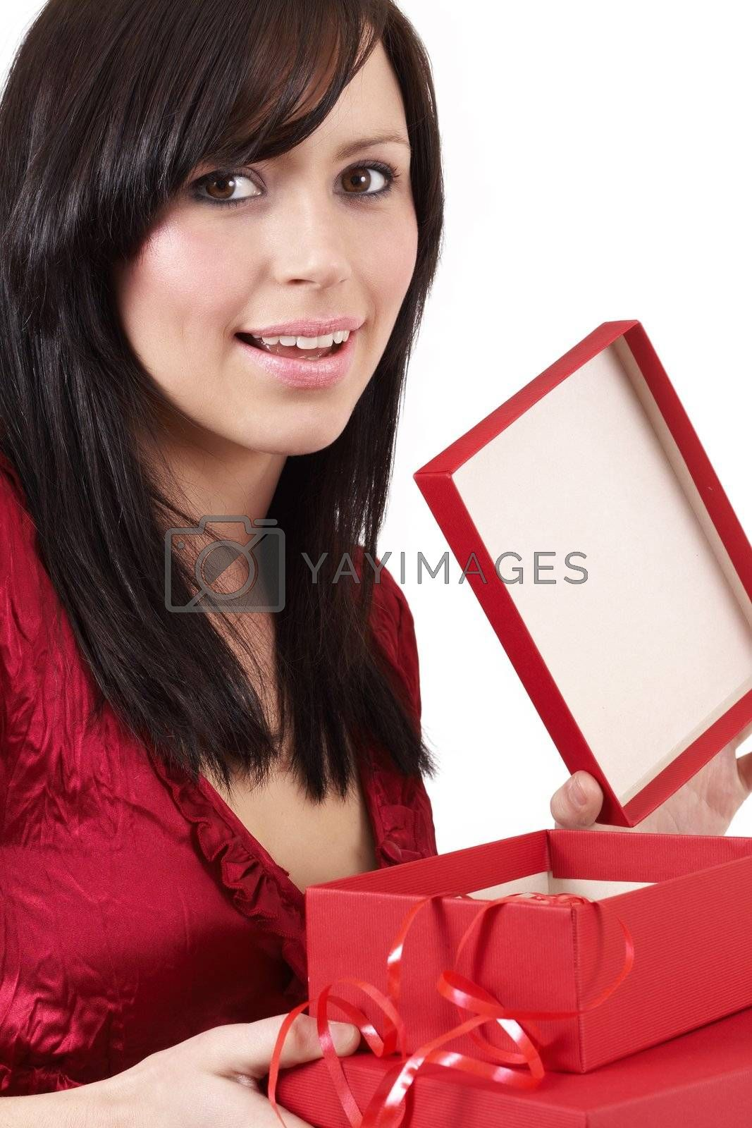 Portrait of a beautiful young brunette woman opening gift boxes at a celebration
