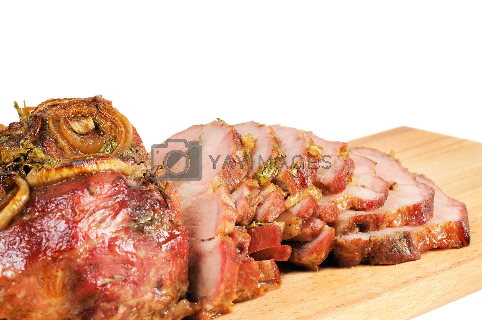 Roast pork on a wooden board. Isolated on white.