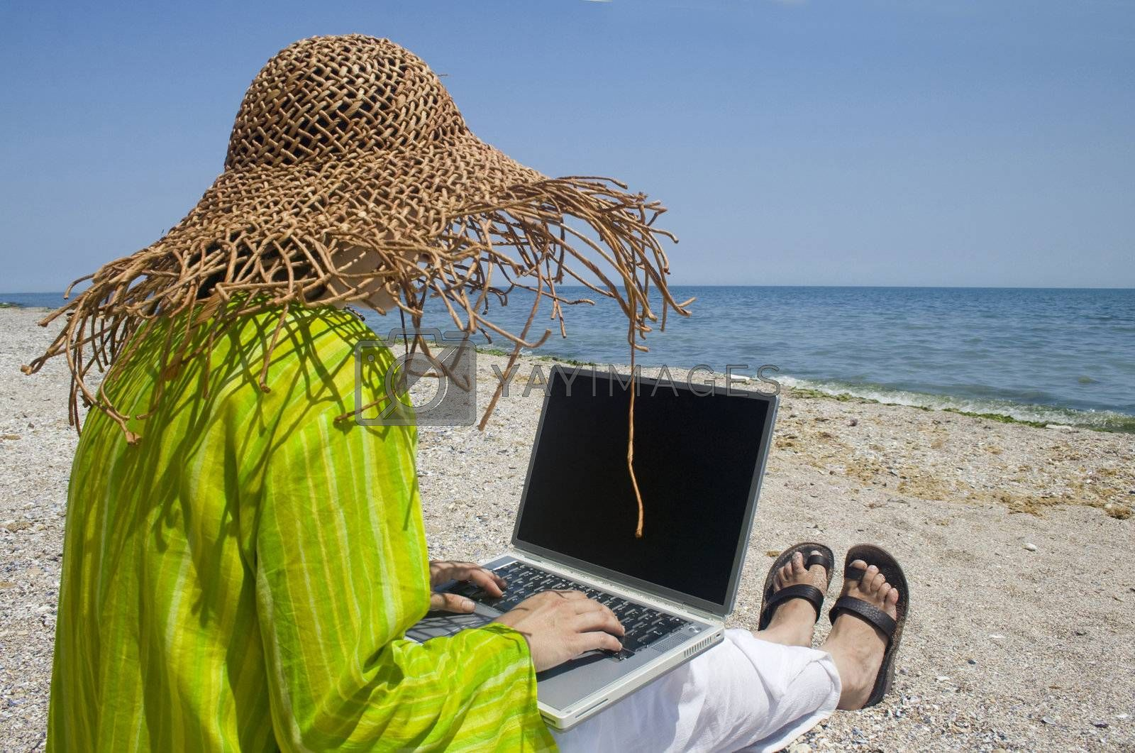 Woman sitting on beach in green top working on laptop