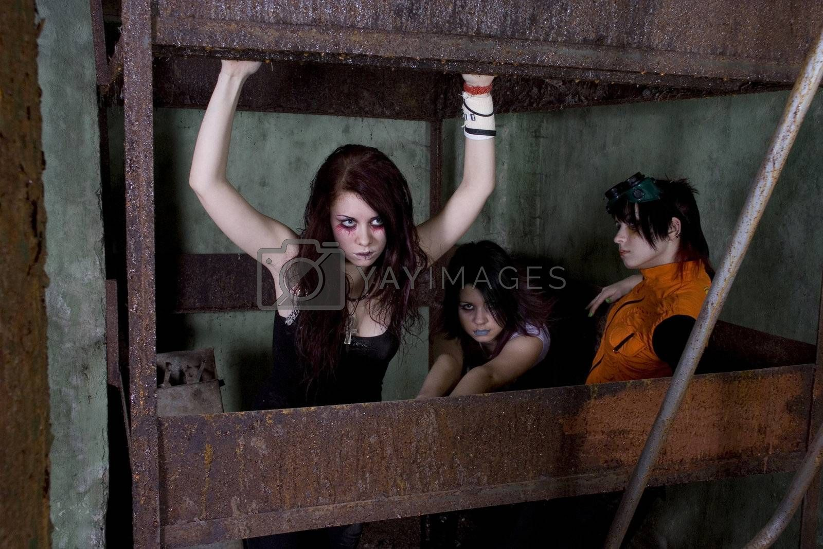 Girls goth in a gloomy cellar in a dirty iron cell