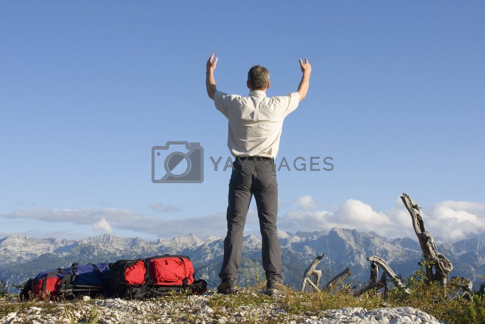 Man with uplifted arms on mountain summit