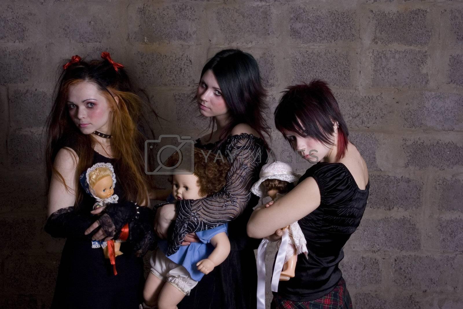 Sad, gloomy girls hold in hands of dolls