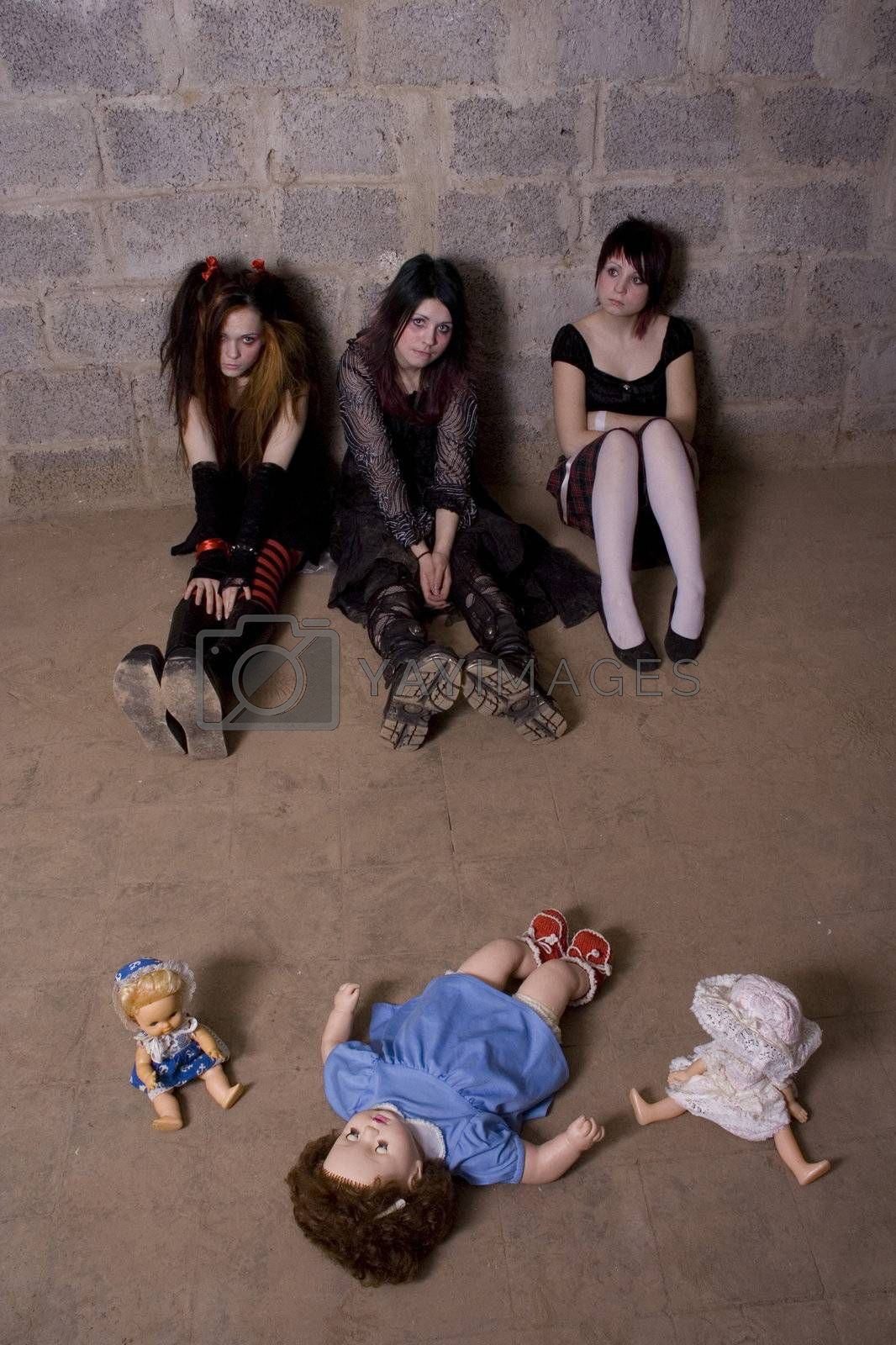 Girls with dolls sit on a floor in depression
