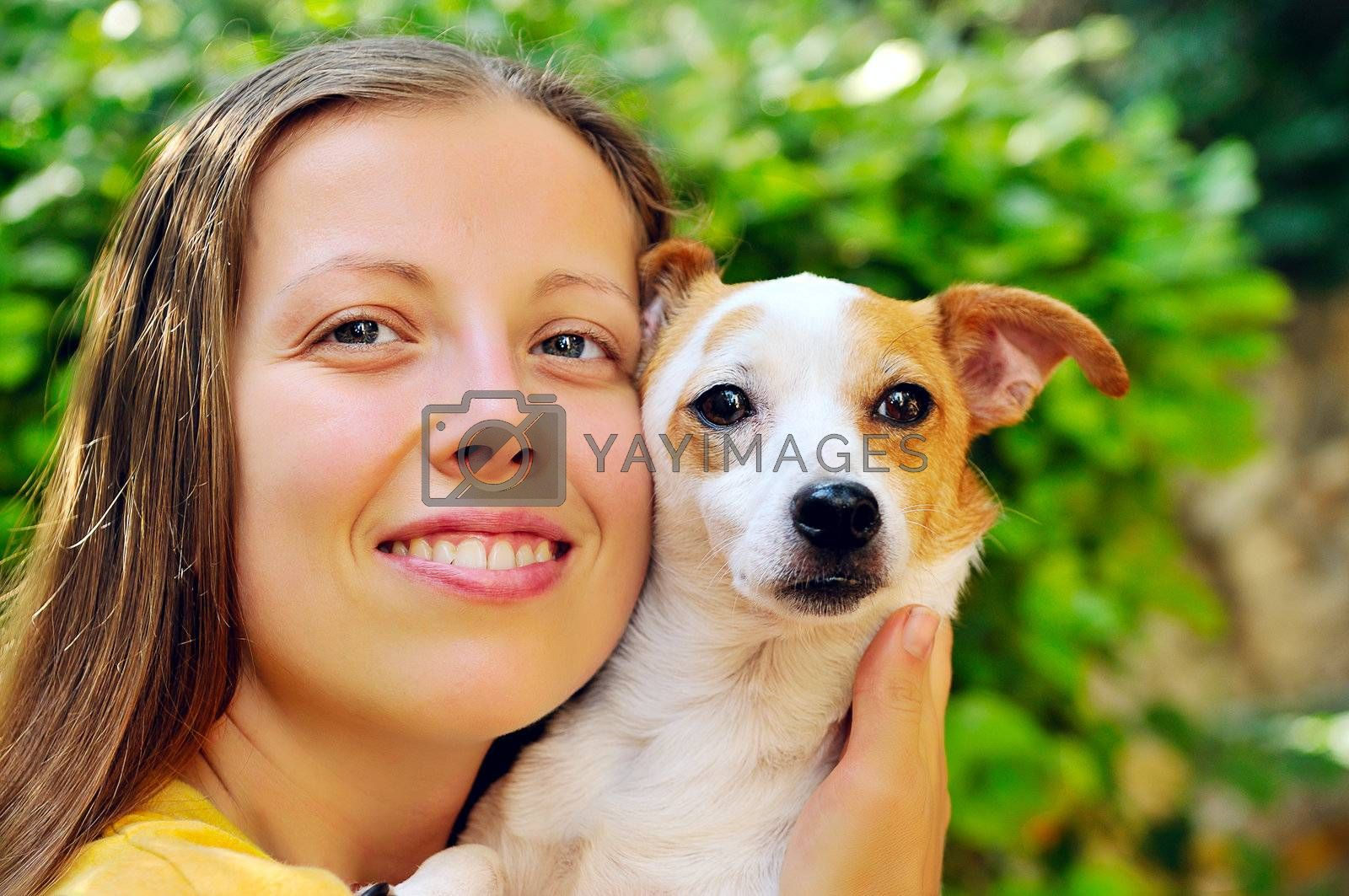 A girl holding a favorite little dog to hold her close