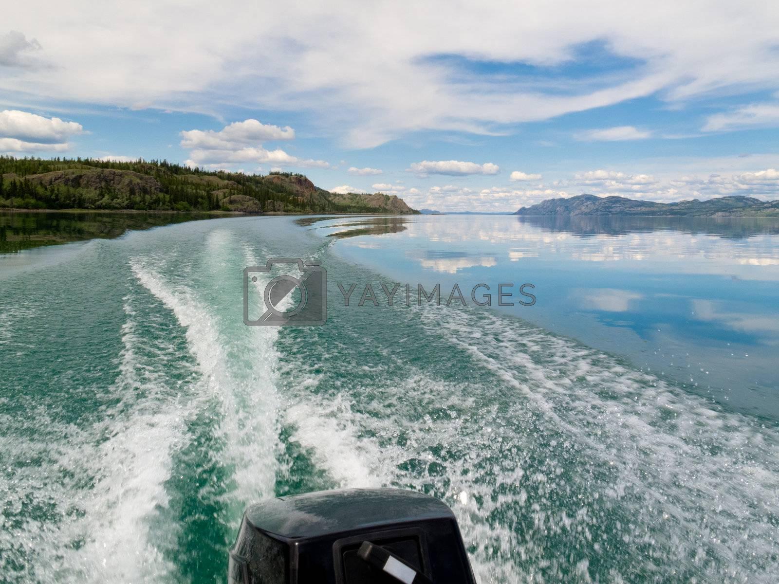 Wake of fast outboard motorboat on beautiful Lake Laberge, Yukon Territory, Canada.