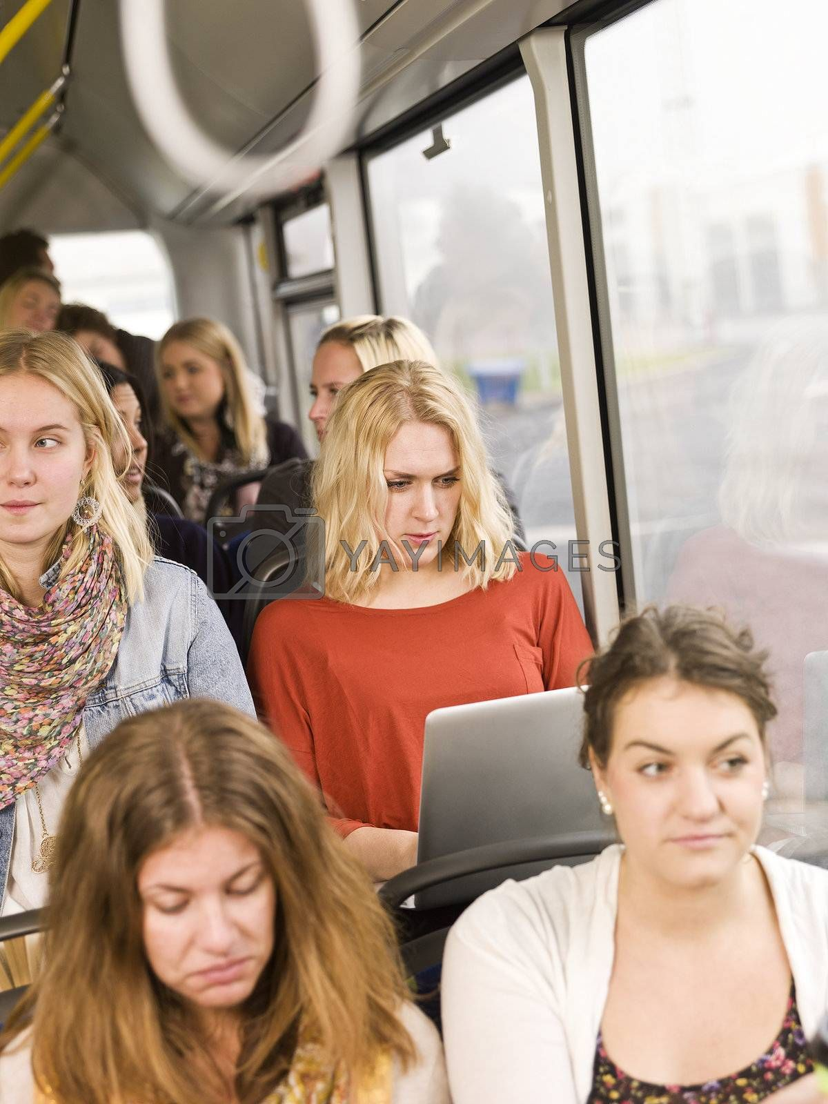 Serious woman on the bus with a computer