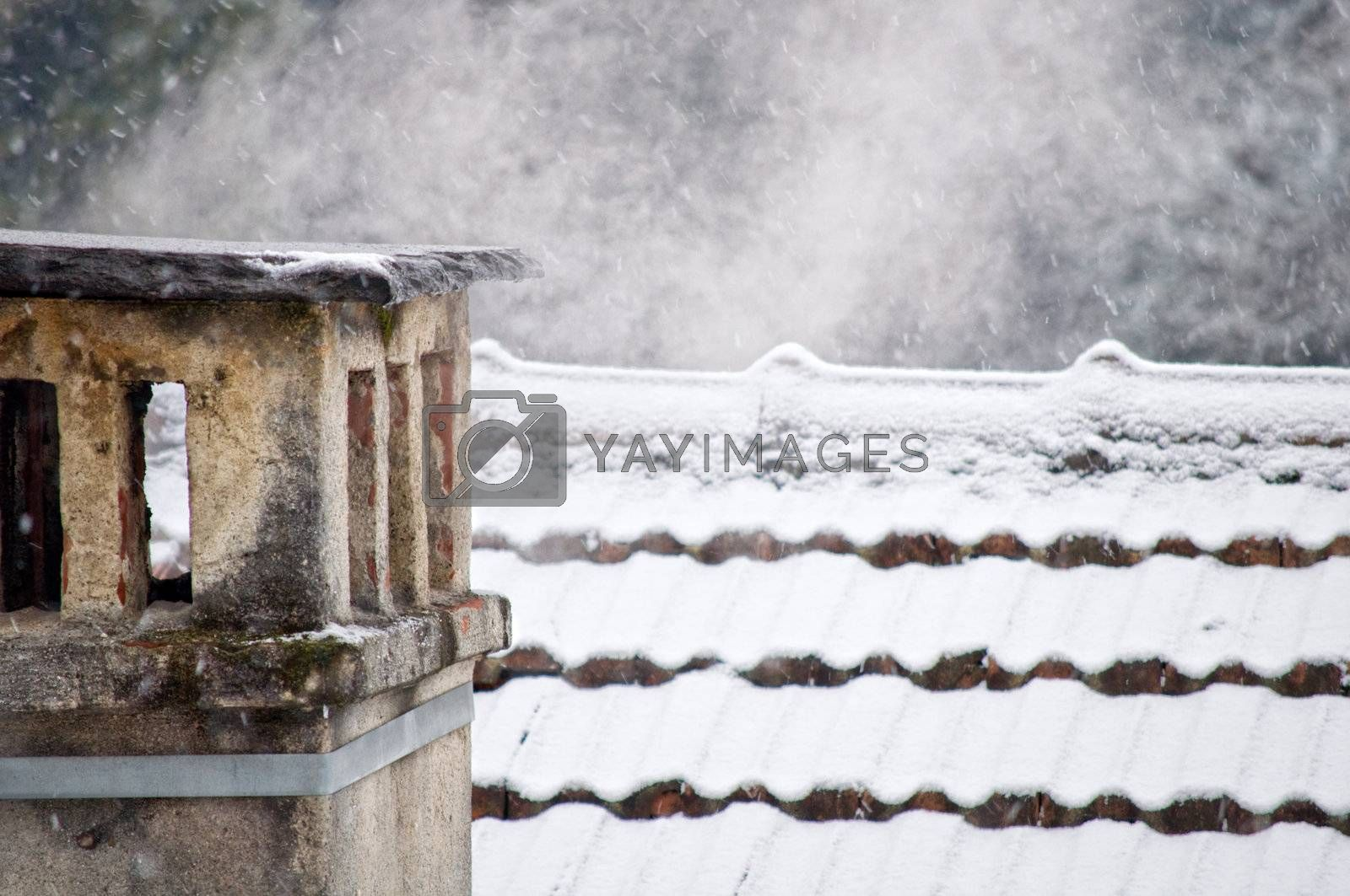 Chimney with smoke on snow covered roof