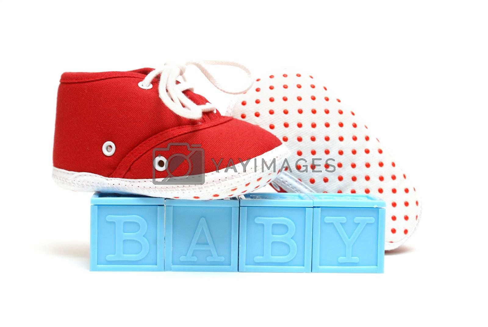The word baby is isolated on white with a pair of red shoes.