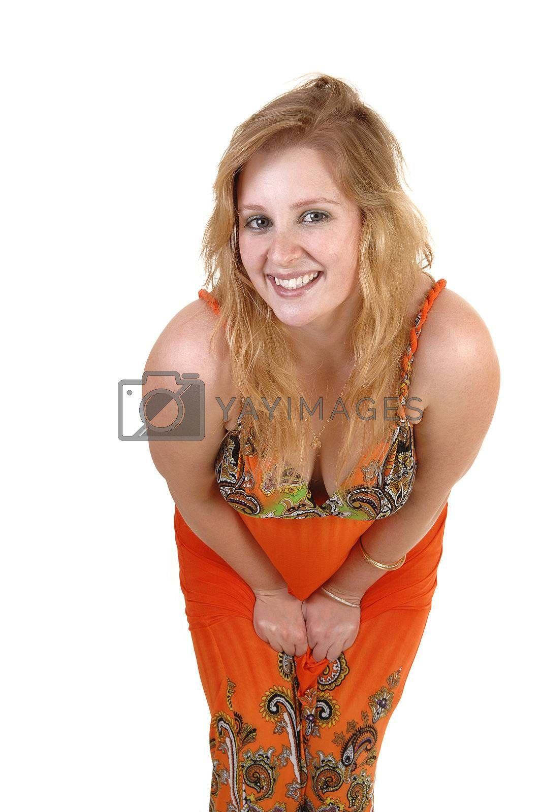 A lovely teenage girl with blond hair and a colorful orange long dress standing and bending down to the camera, over white background.