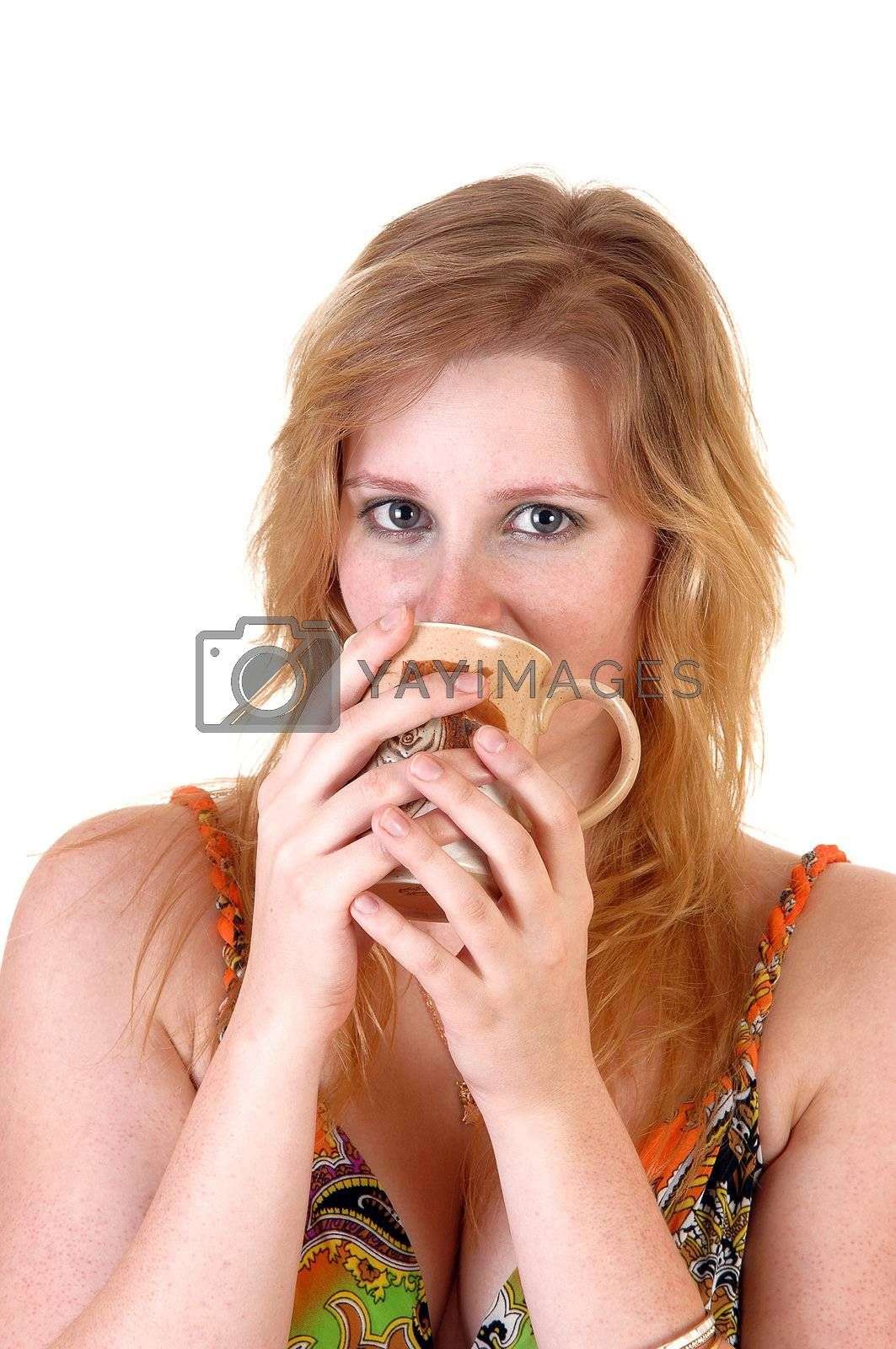 A beautiful blond teenager girl looking into the camera and drinking her coffee from a mug, in an colorful dress over white background.