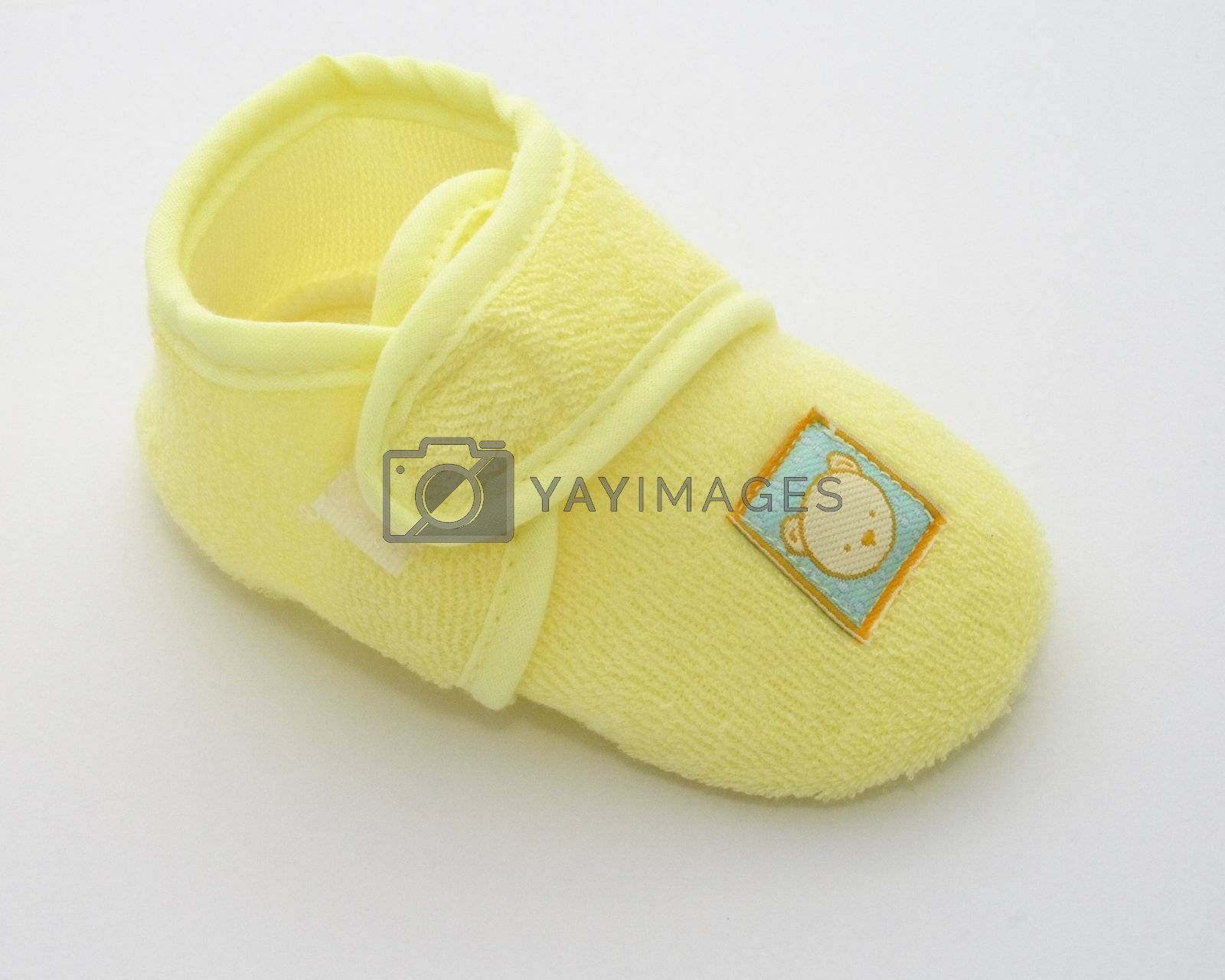 one babies shoe in a yellow towelling fabric