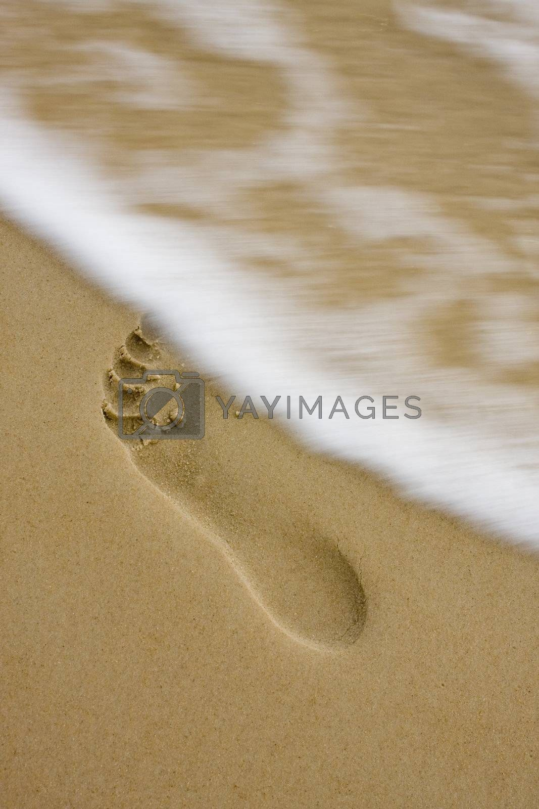 Footprint on the beach with little motion blurred wave