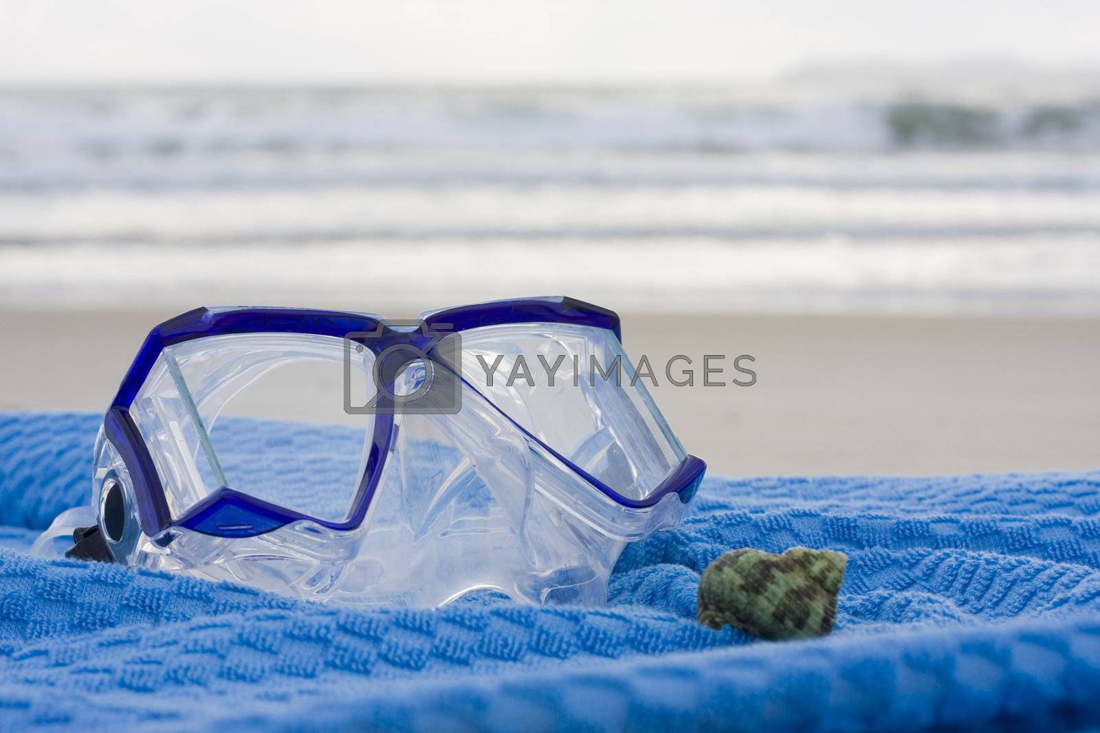 Diving mask and shell on a blue towel on the beach