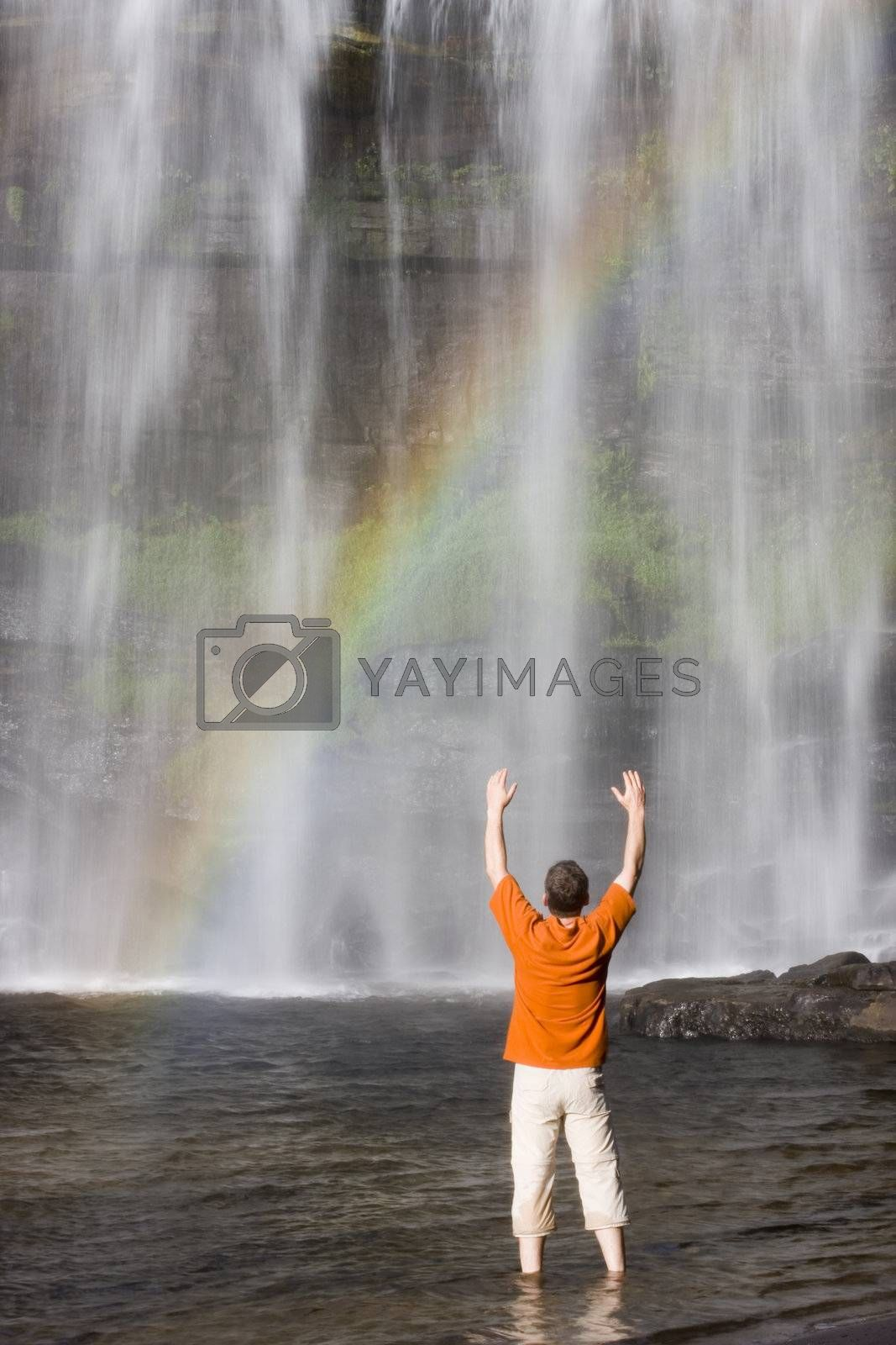 Man with uplifted arms standing in the water in front of a tropical waterfall with rainbow - Brazil