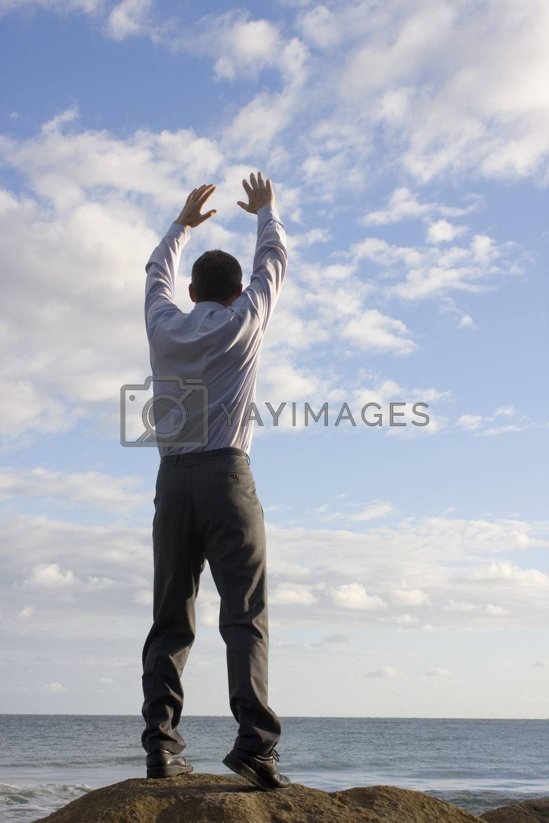 Happy businessman with uplifted arms on the beach