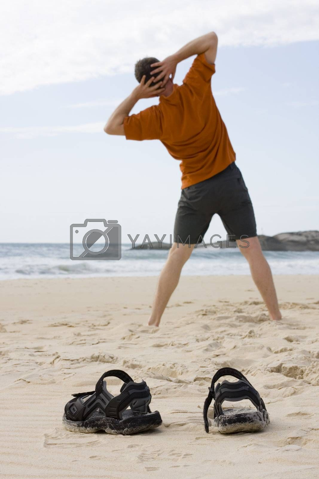 Man doing gymnastics on the beach. Focus on his sandals in the foreground