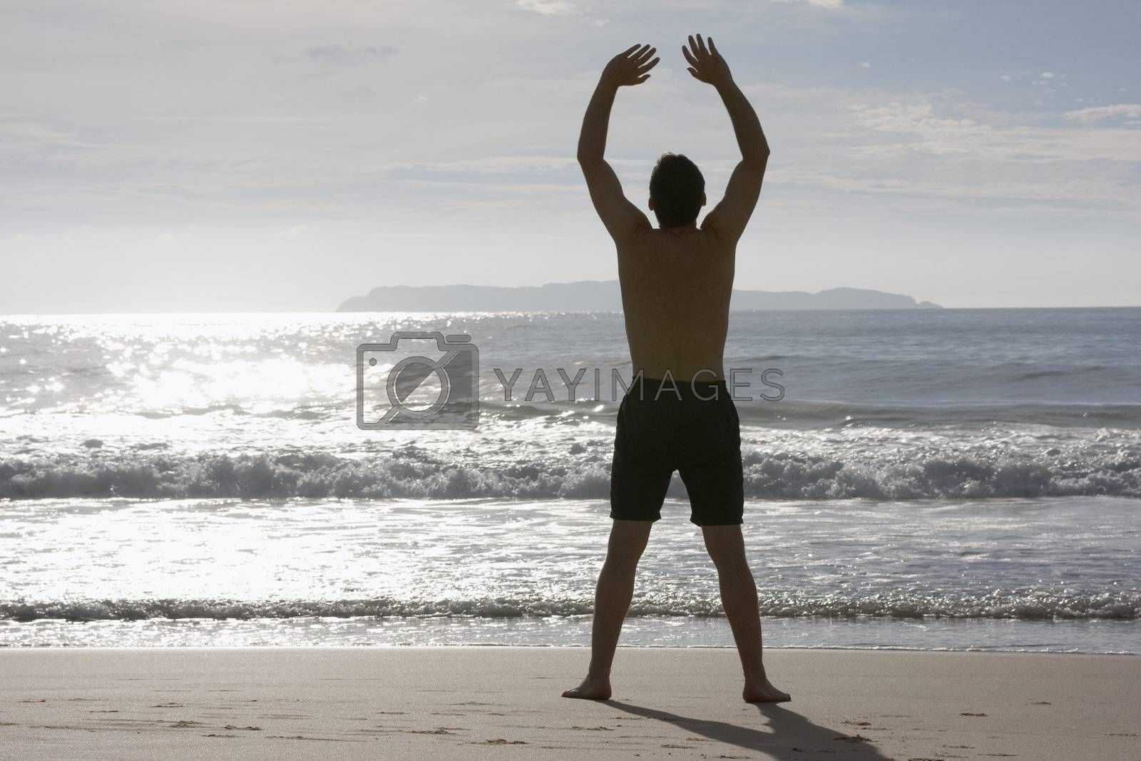 Man doing yoga on the beach by ArtmannWitte