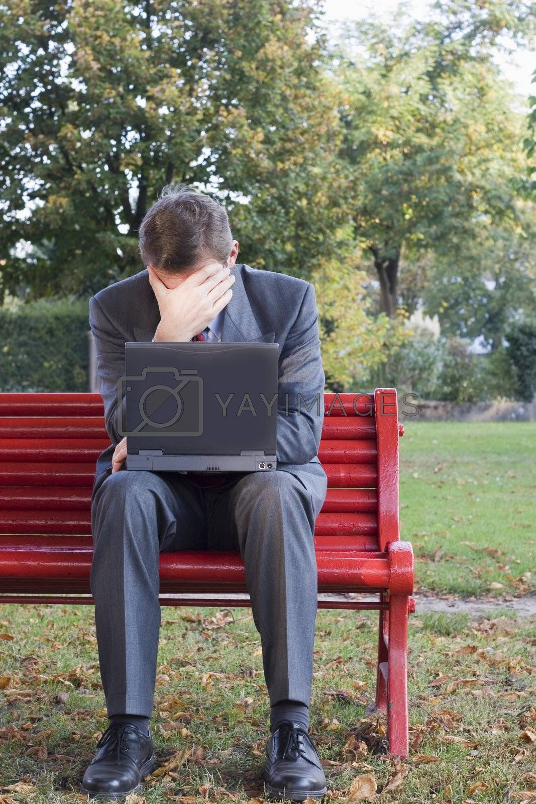 Tired businessman with laptop sitting on a park bench