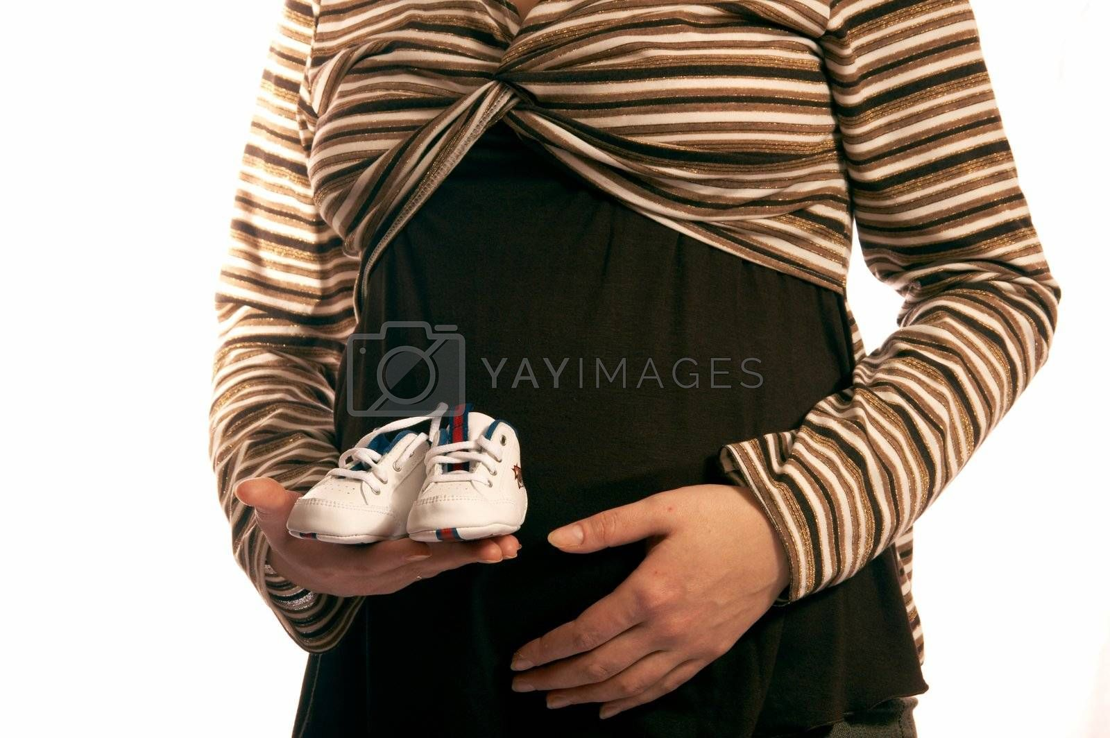 The pregnant woman on a white background. In hands holds small boots