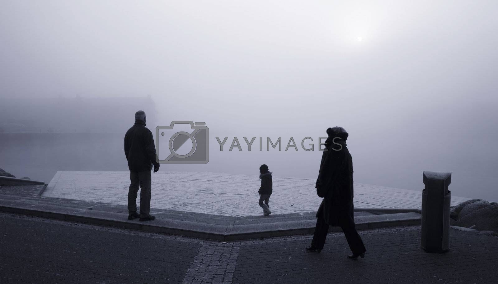 An active family by the waterfront of Nyborg, Denmark a cold foggy winter morning.