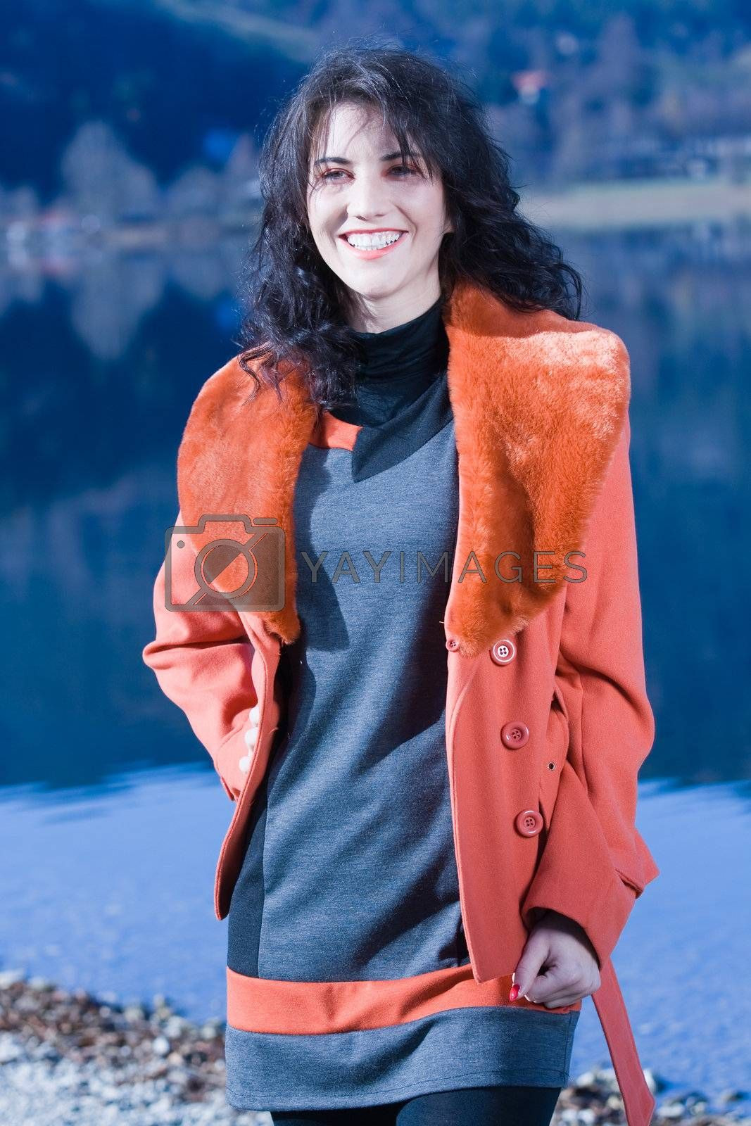 Very beautiful model in fashionable clothing at Autumn Lake