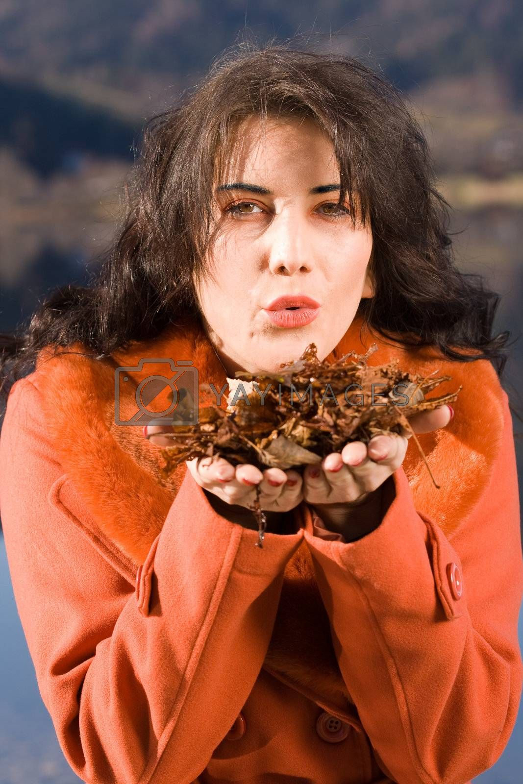 Young woman blowing leaves from your hand