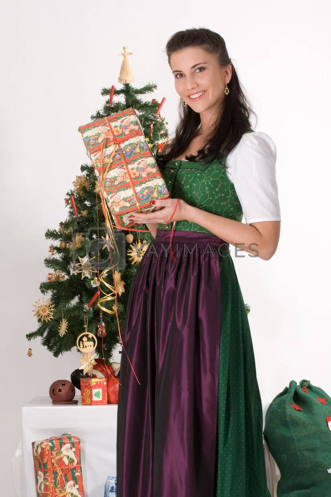 Bavarian girl with Christmas parcels before a table with Christmas gifts