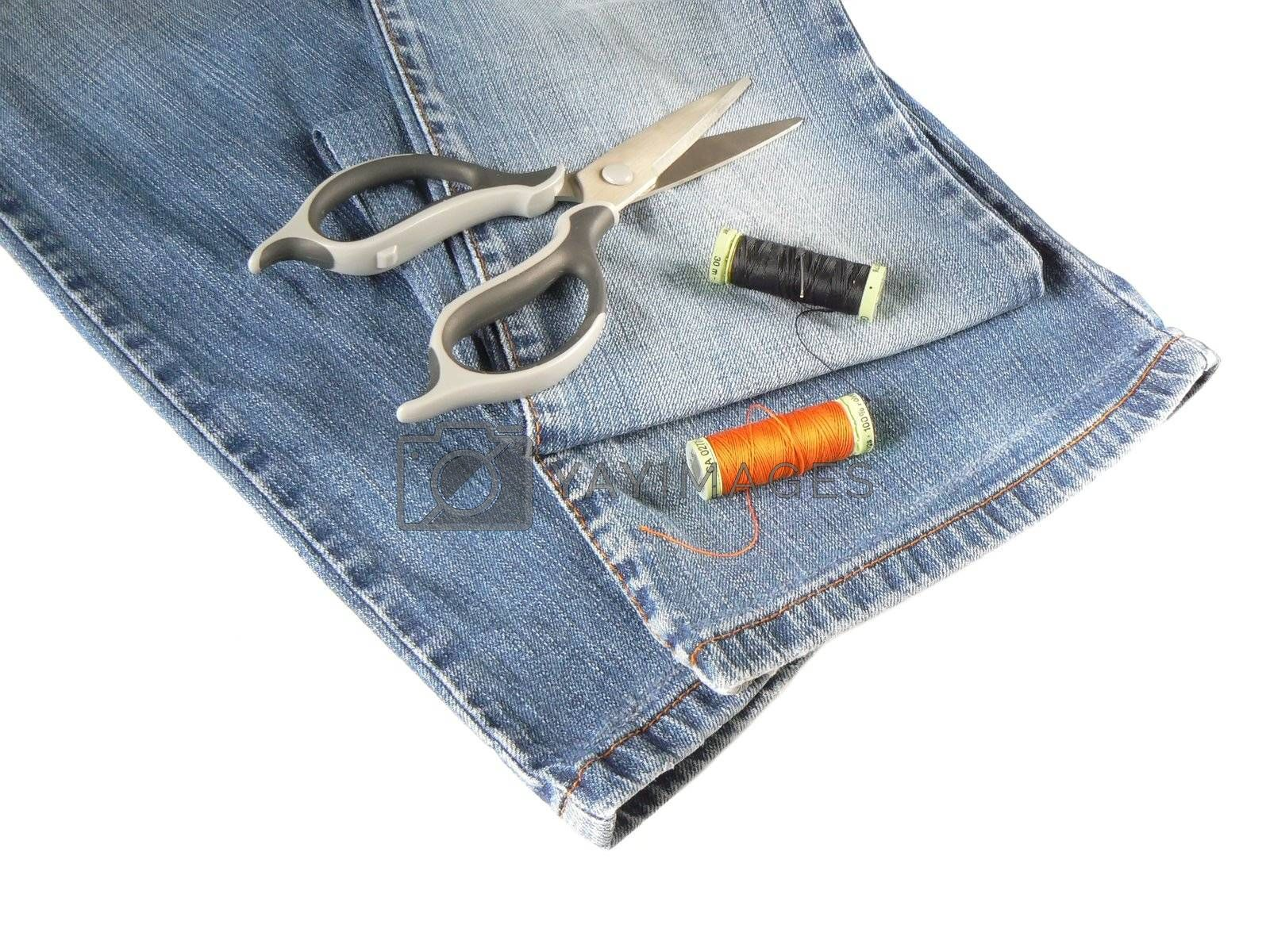 sewing accessorys and jeans on white background