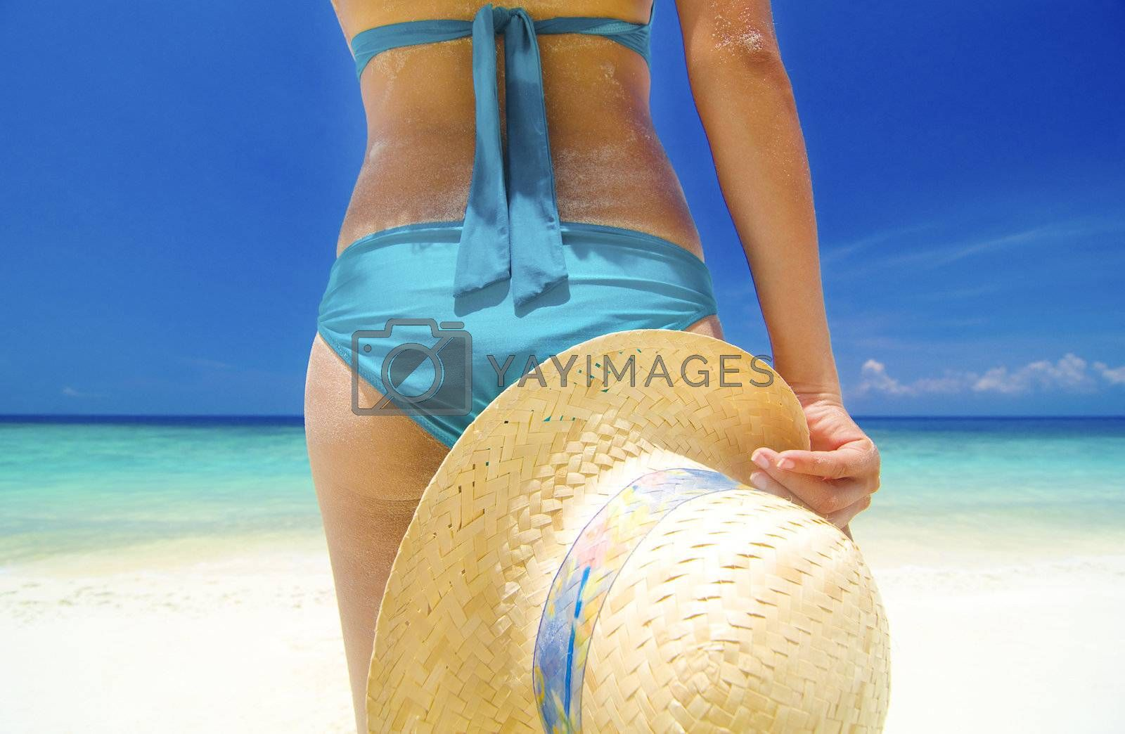 Woman standing on a tropical beach wearing a bikini and holding a hat