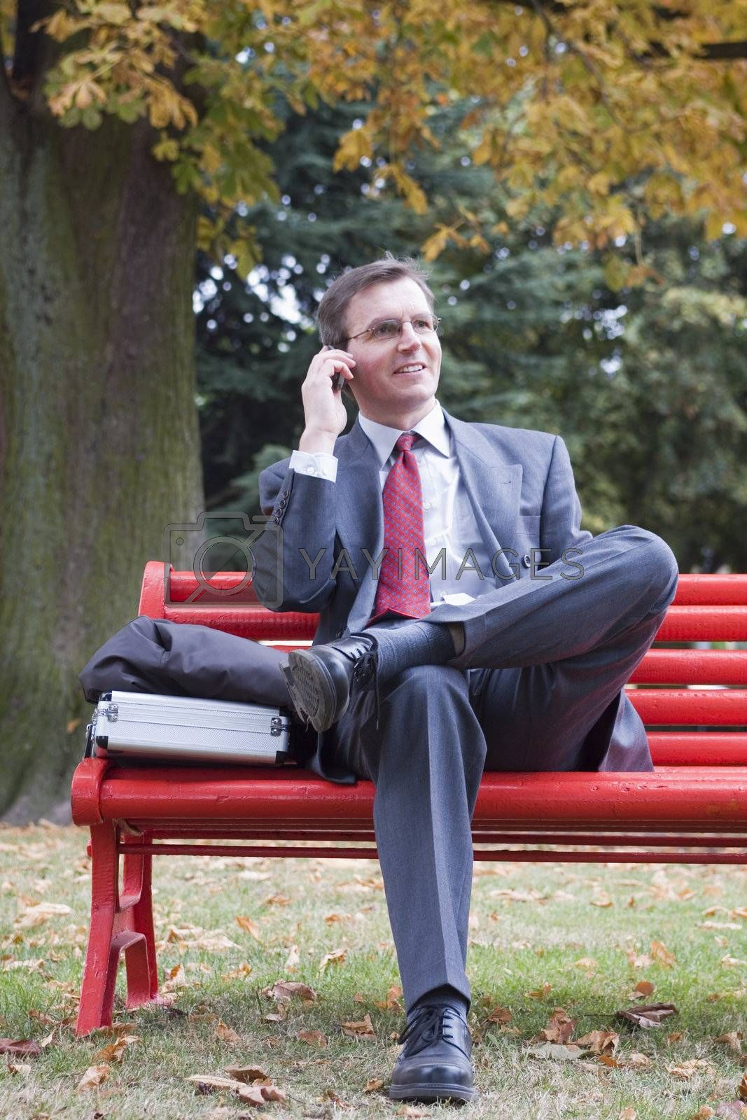Businessman talking on cell phone while sitting on a red park bench