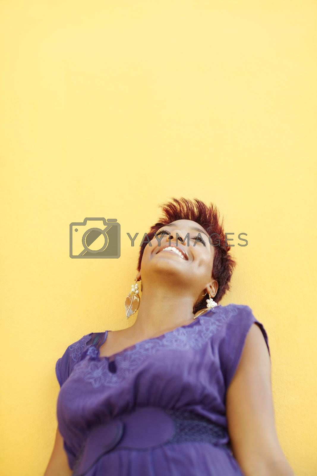 portrait of african college student smiling and looking up with yellow wall in background. Selective focus, copy space