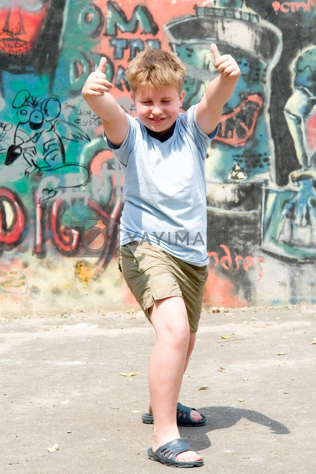 A smiling child with graffiti at background