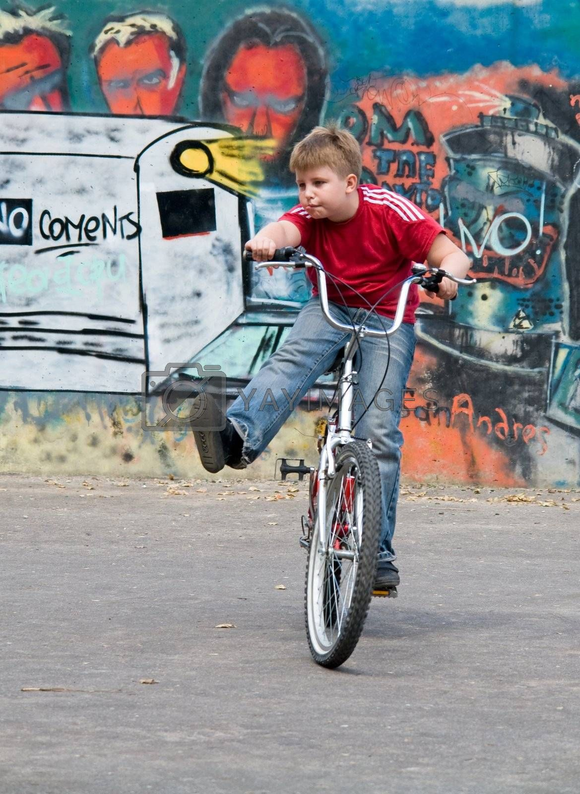 boy on a bicycle with graffiti at background