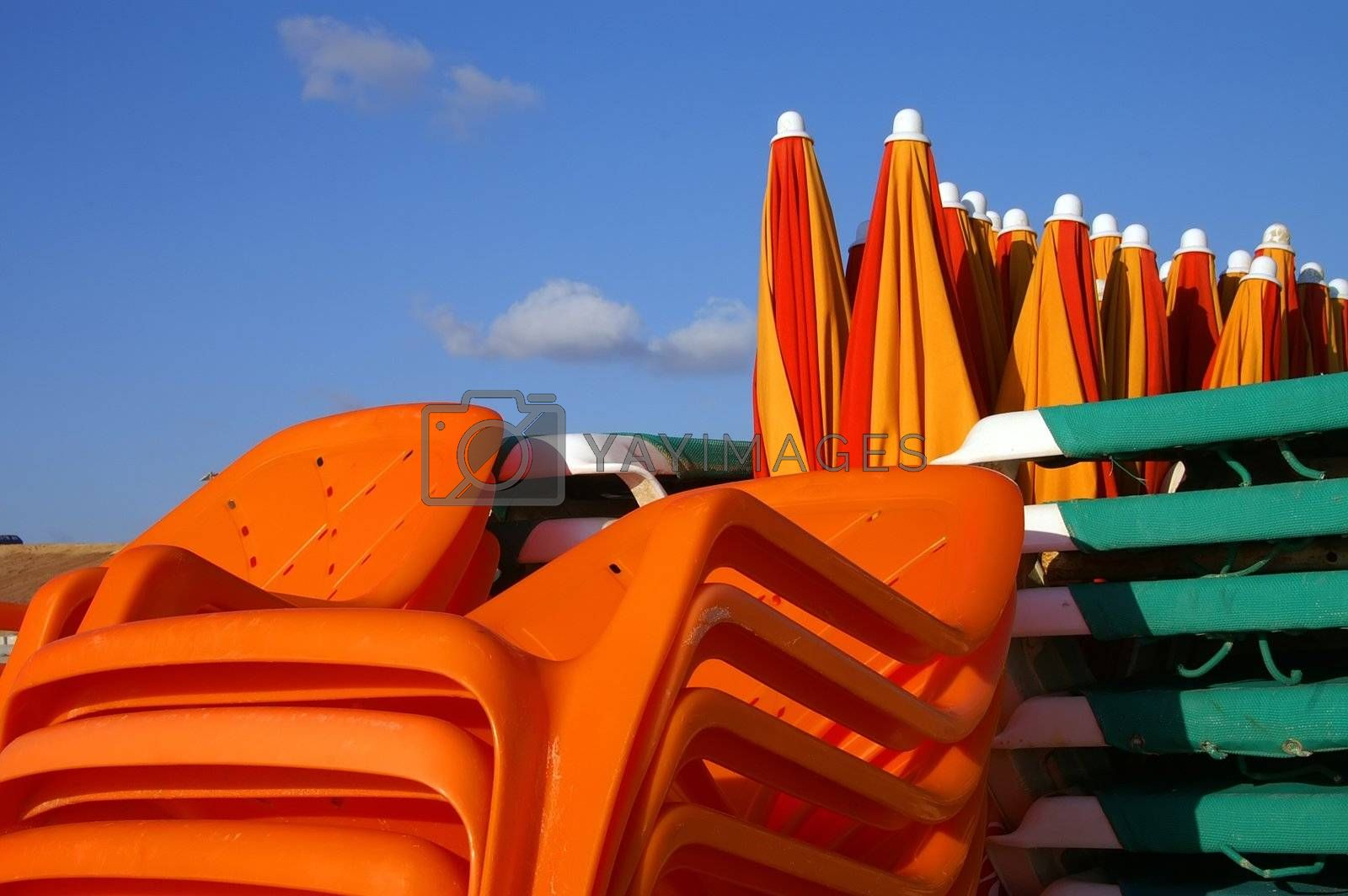 bunch of beach plastic chairs and sun blockers