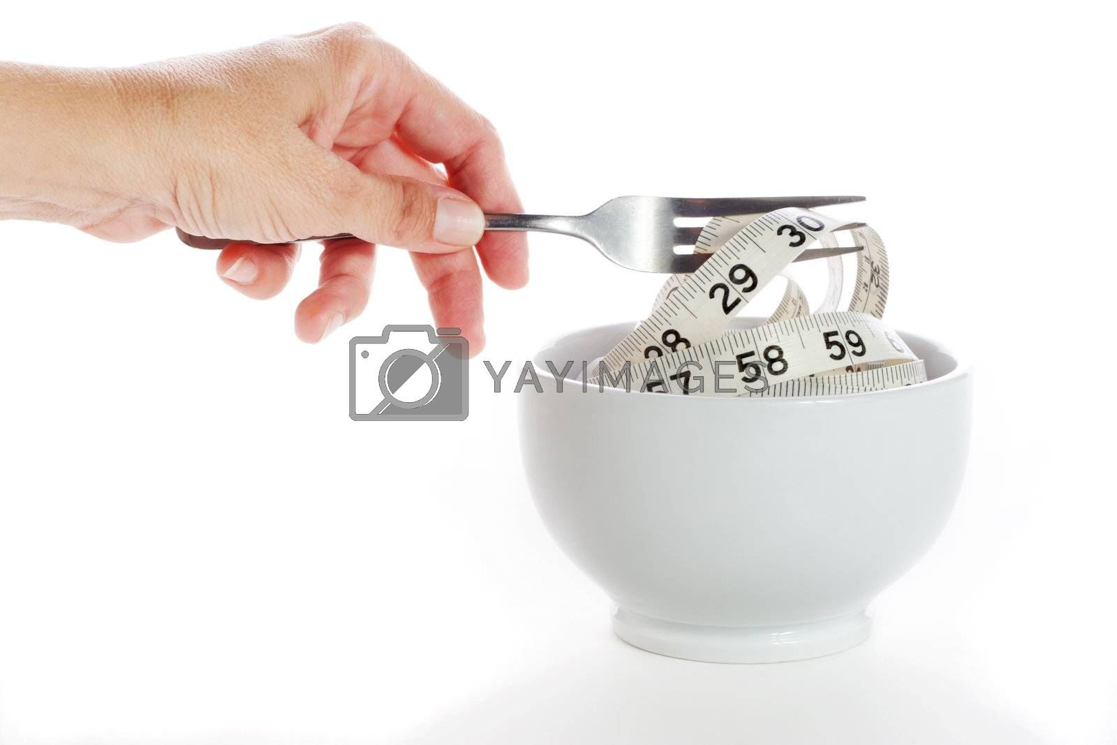 A woman's hand picks up a fork full of a tape measure from a white cup