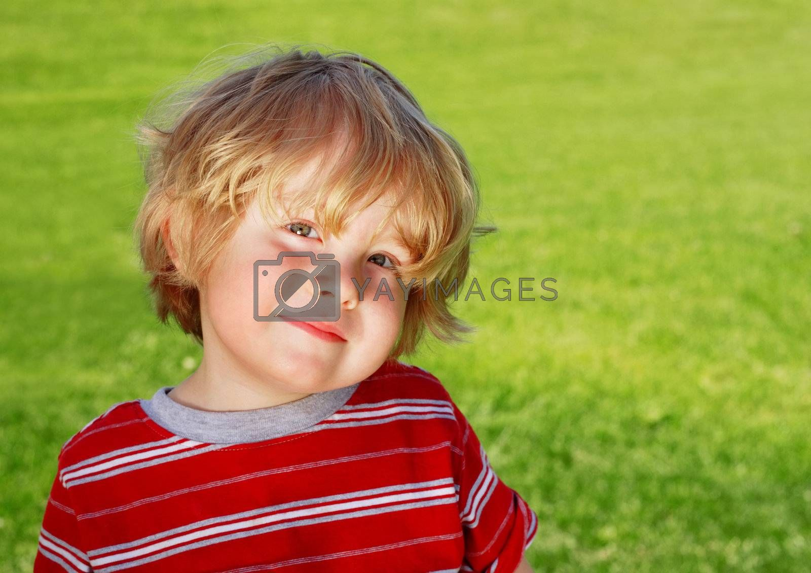 A young boy smiles at the camera while sitting on the grass