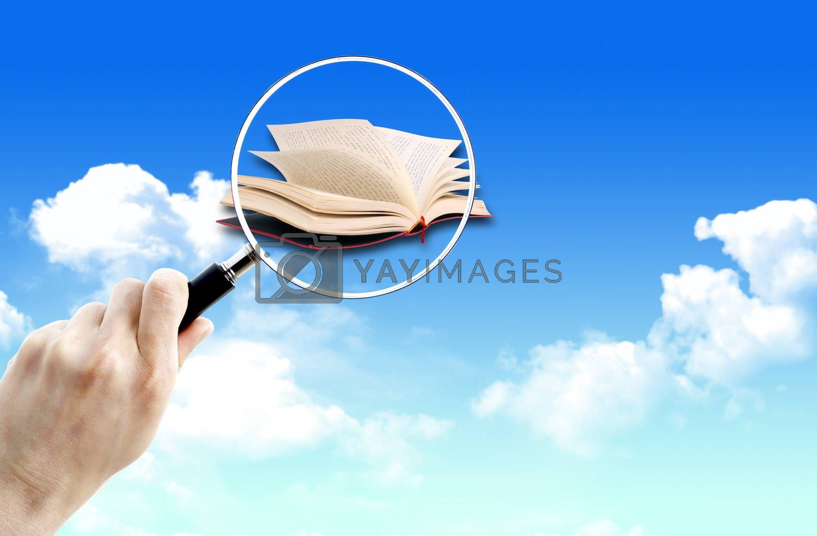 Magnifying glass over of book on the sky