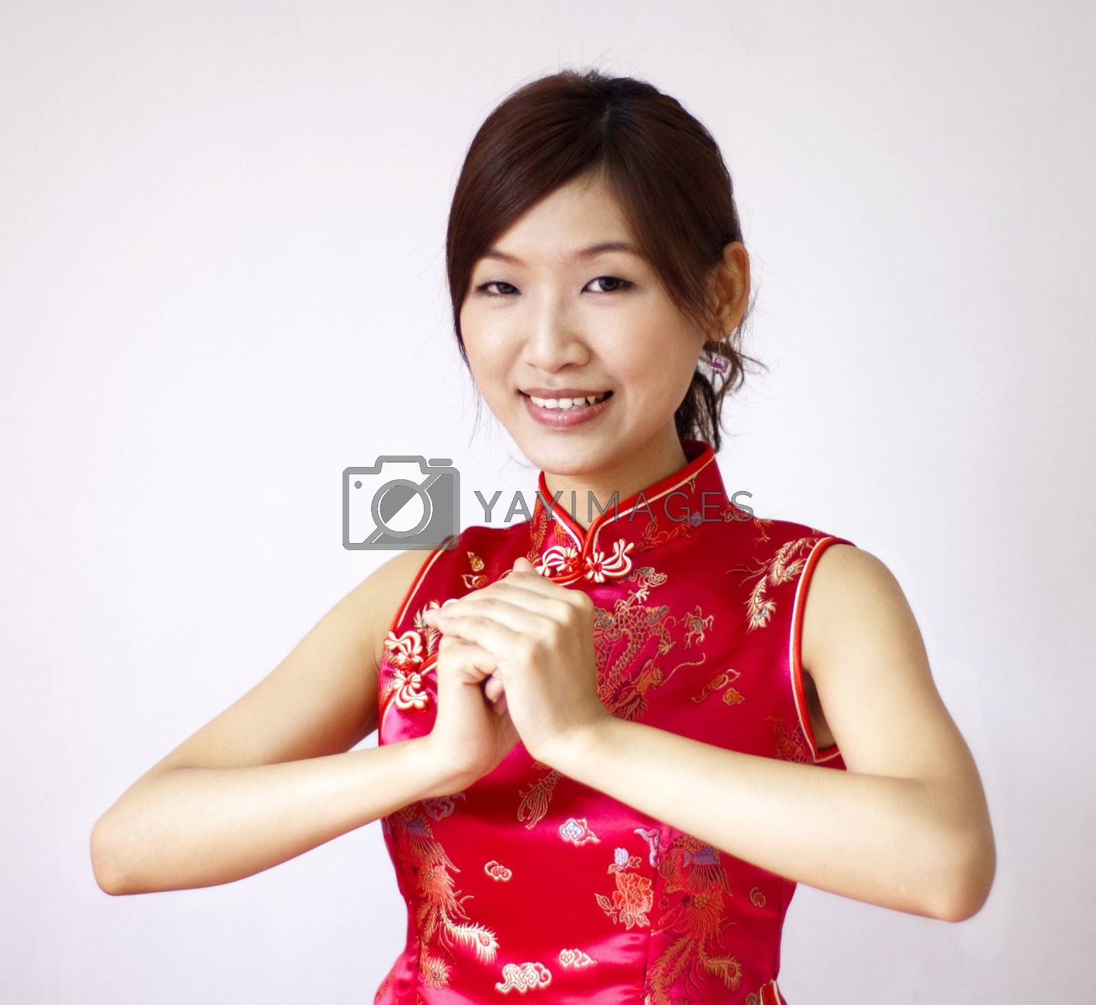 Oriental girl with traditional Cheongsam suit wishing you a happy Chinese New Year.