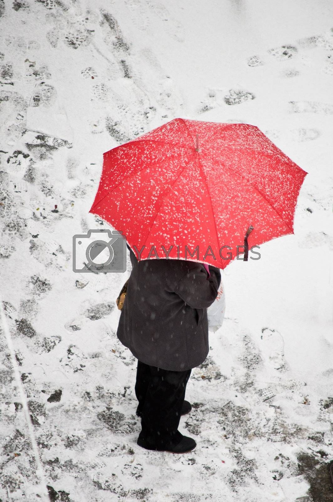 Woman with red umbrella standing on a snow covered sidewalk